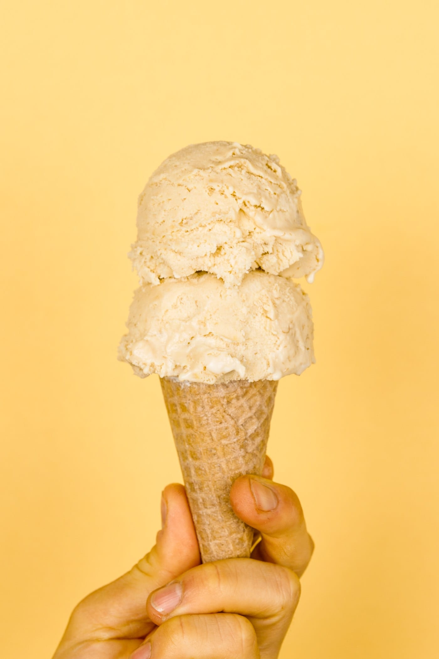 Two scoops of banana cream pie ice cream in ice cream cone held by a hand with light peach colored background