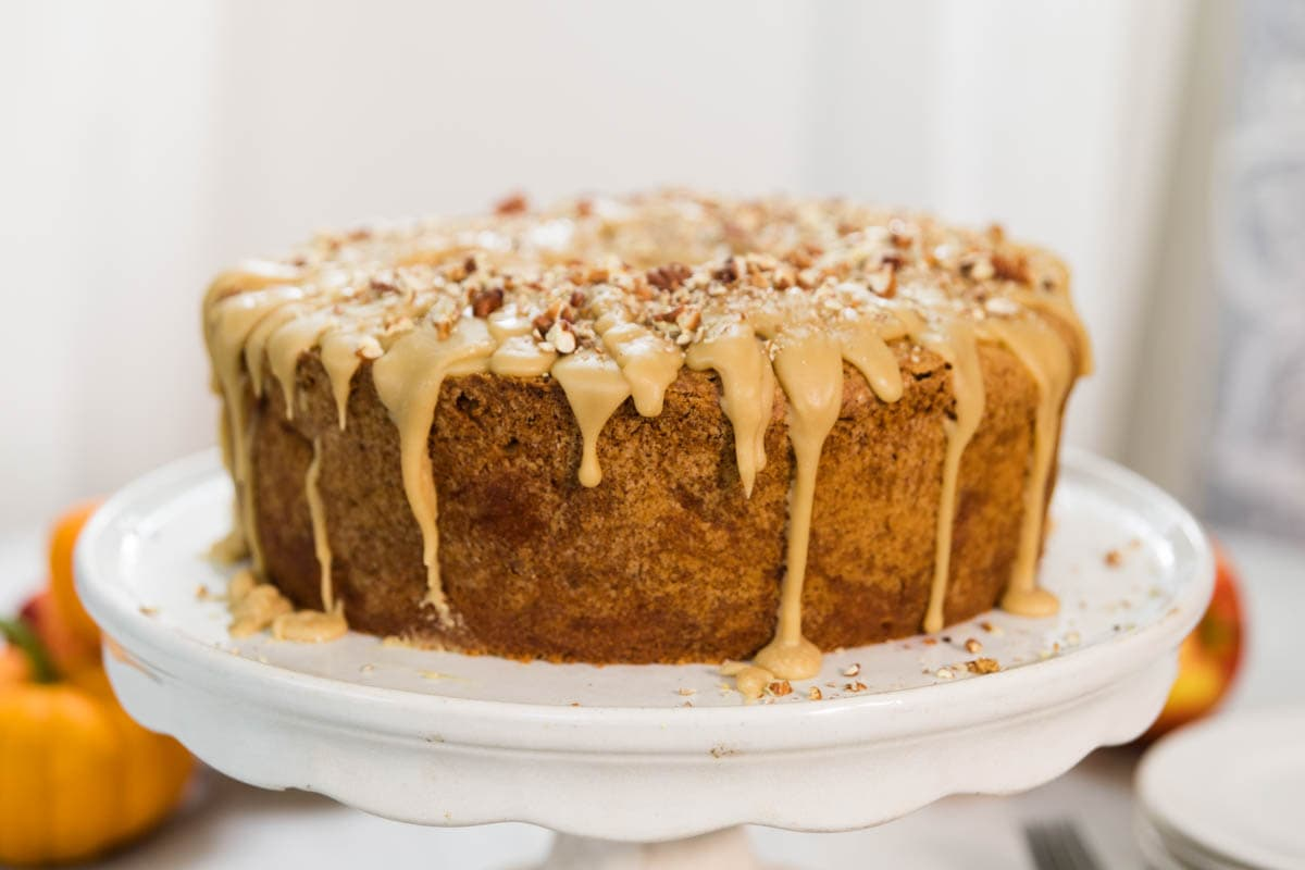 Circular brown apple spice cake sitting on white cake stand with glaze dripping down sides with orange pumpkins and apples in the background