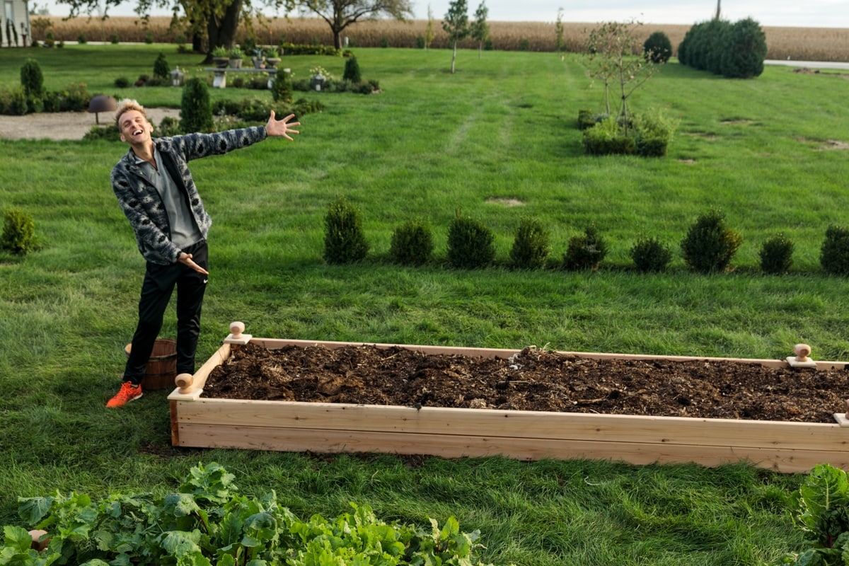 Man with blonde hair standing beside completed raised garden bed filled with dark brown soil with grass all around