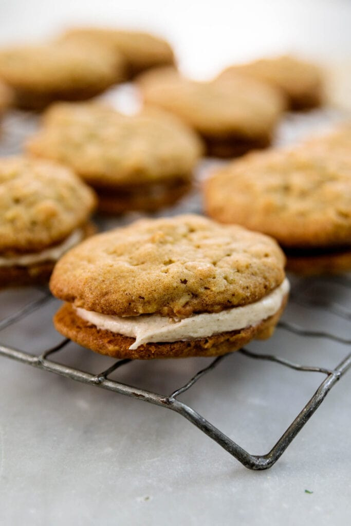 Two oatmeal spice cookies sandwiching a layer of white creme filling with multiple cookies in background all on a wire cooling rack on a marble surface