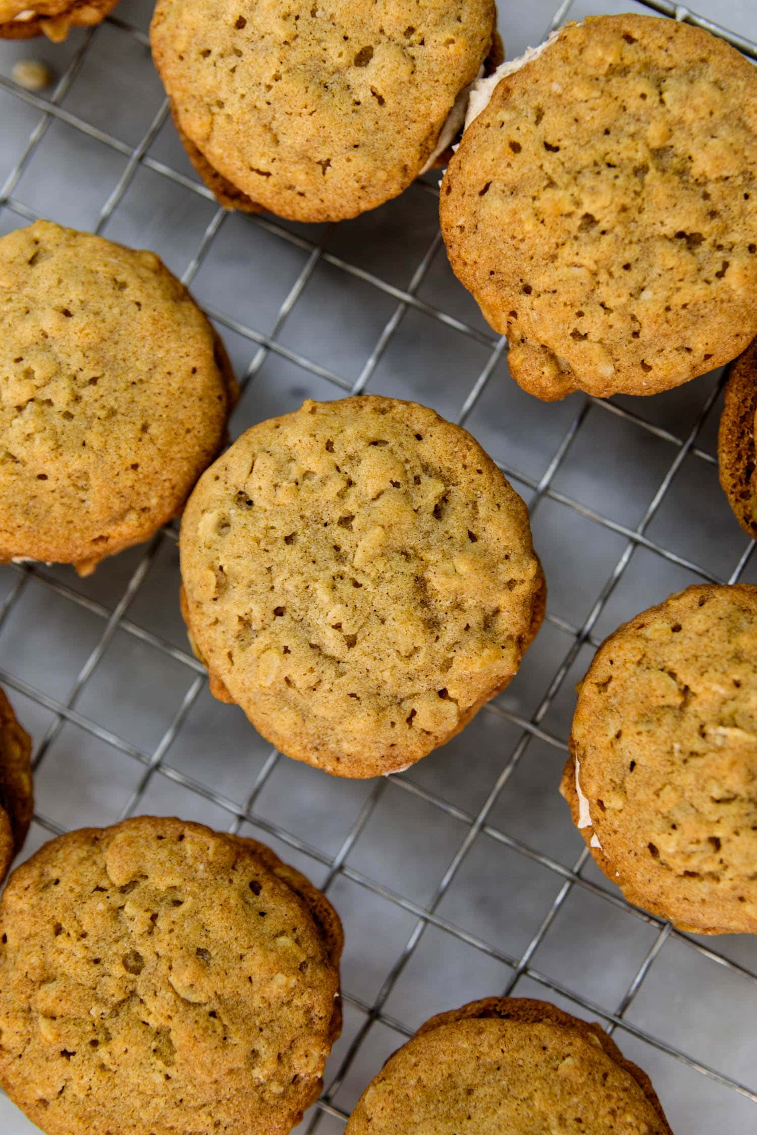 Top down view of oatmeal spice creme-filled cookies all on a wire cooling rack on a marble surface