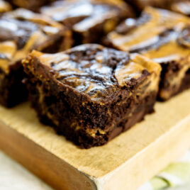 Pumpkin cheesecake brownies on a wood cutting board with white and green napkin underneath