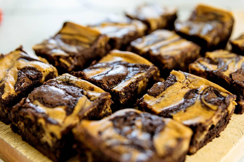 Pumpkin cheesecake brownies on a wood cutting board