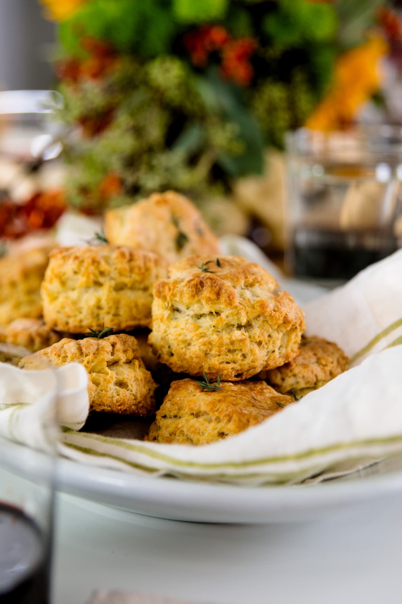Herb cheese biscuits sitting on white and green linen in white bowl with flowers in background and glass in foreground all on white surface