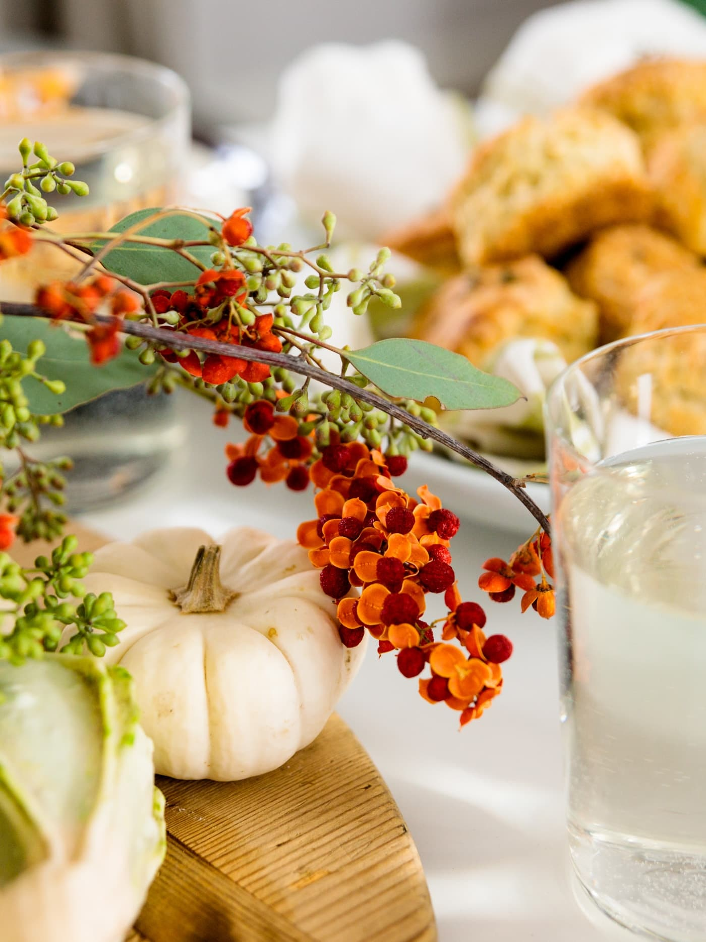 Herb cheese biscuits in background with bittersweet arrangement and white pumpkins in foreground all on white surface