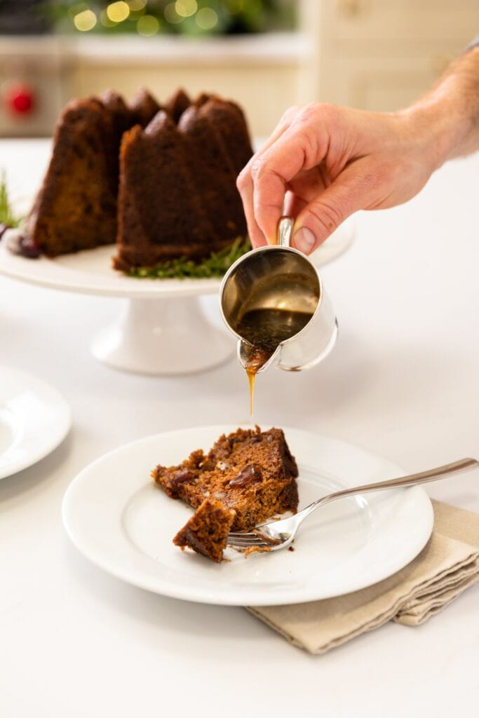 Hand pouring sauce onto piece of brown cake sitting on white plate with rest of cake in background all on white surface