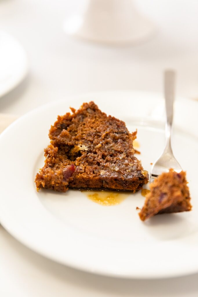 Piece of date pecan cake sitting on white plate with fork holding piece all on white surface