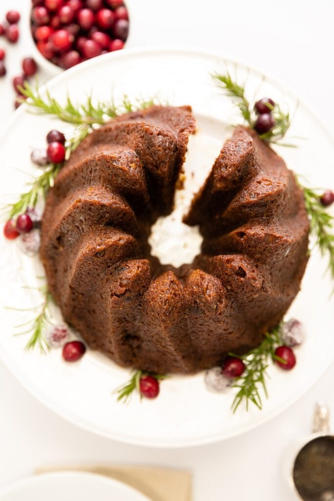 Top down view of brown cake made in Bundt pan sitting on white cake plate with cranberries sitting in bowl and piece of cake to side all on white surface
