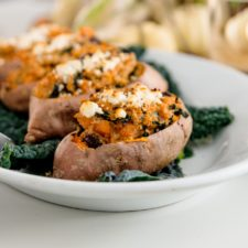 Twice baked sweet potatoes on bed of kale sitting on white plate with white pumpkins in background on white surface