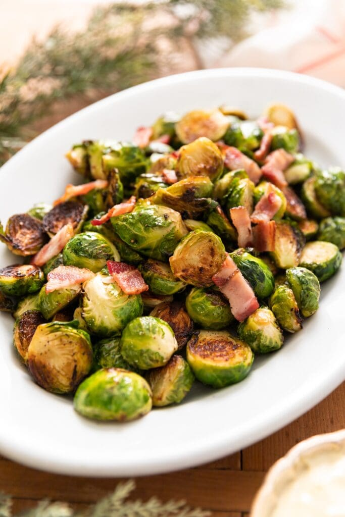 White platter filled with Brussels sprouts and topped with bacon with greenery in background all on wood board