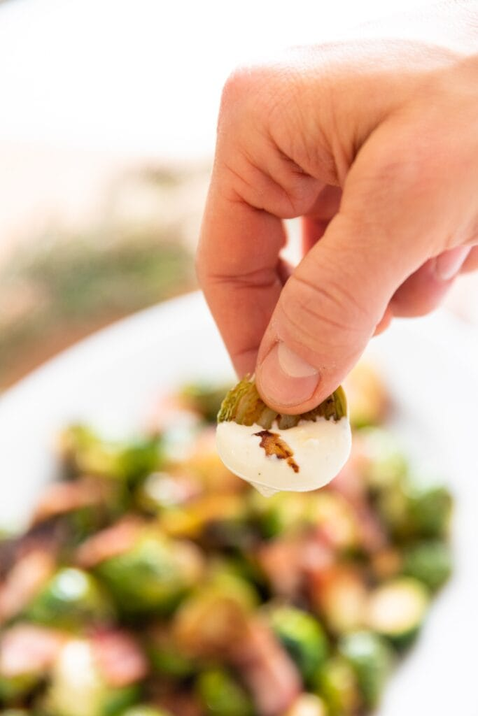 Hand holding green Brussels sprout with white creamy sauce on the end with rest of Brussels sprouts in background