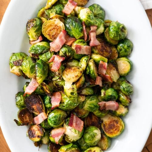 Top down view of Brussels sprouts in white bowl topped with bacon sitting on wood board
