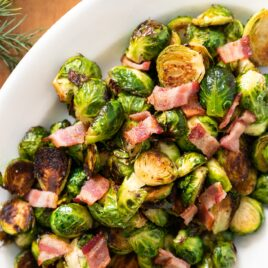 Top down view of green Brussels sprouts sitting in white platter topped with bacon sitting on wood board with greenery