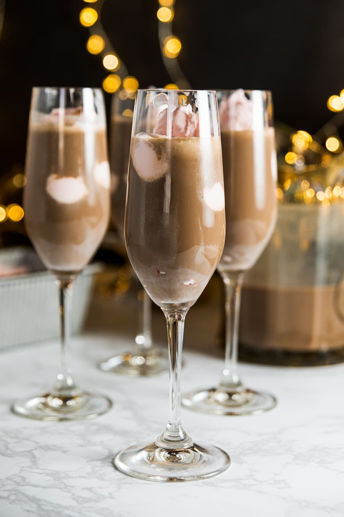 Three champagne flutes filled with pink peppermint ice cream and chocolate coffee mixture sitting on marble surface with Christmas lights on black background