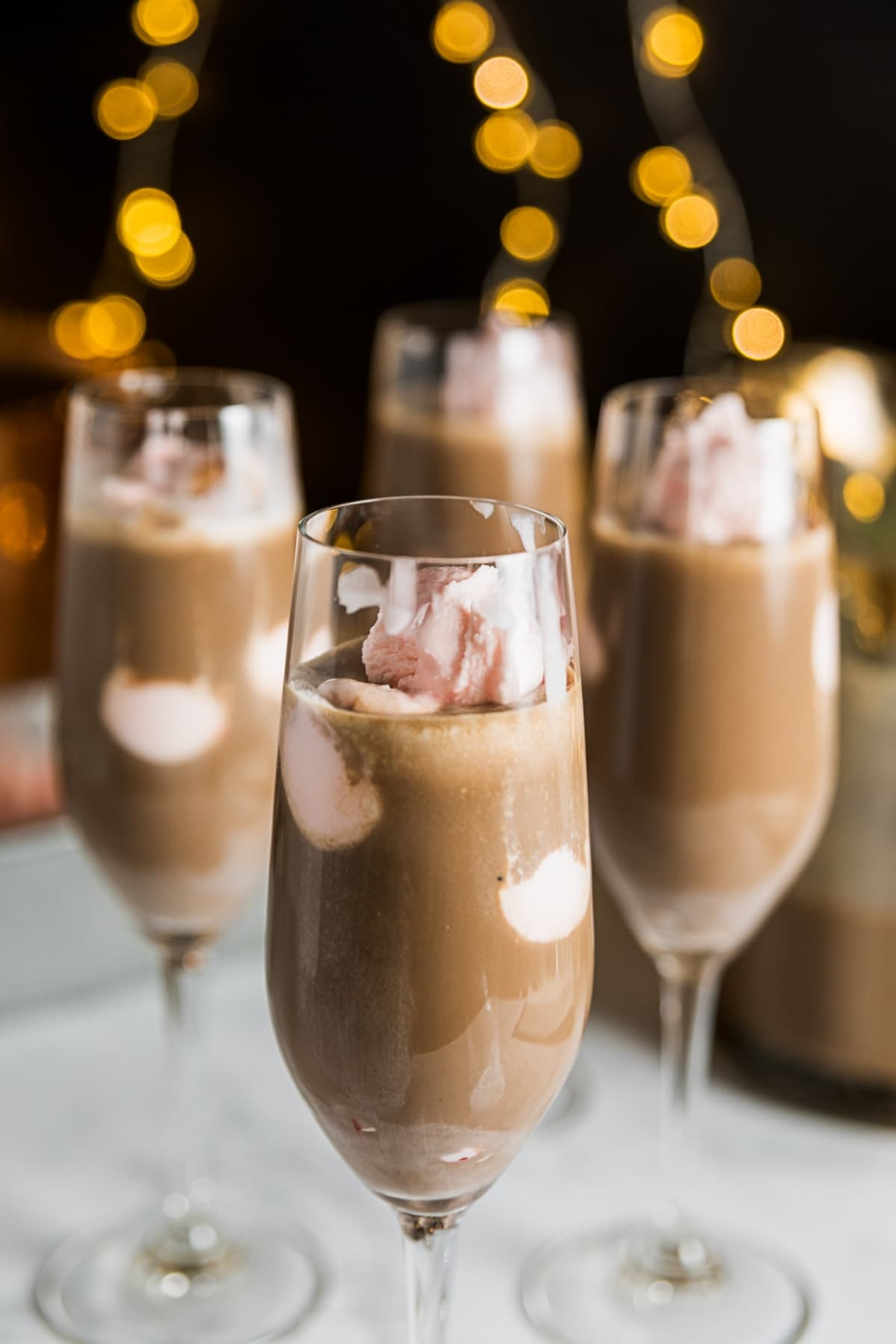 Four champagne glasses filled with chocolate mixture with pink ice cream floating all with black background with twinkling Christmas lights