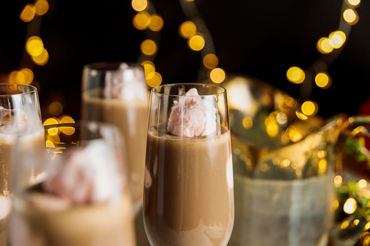 Yellow twinkling lights against black background with champagne flute filled with pink ice cream and chocolate coffee cooler in foreground