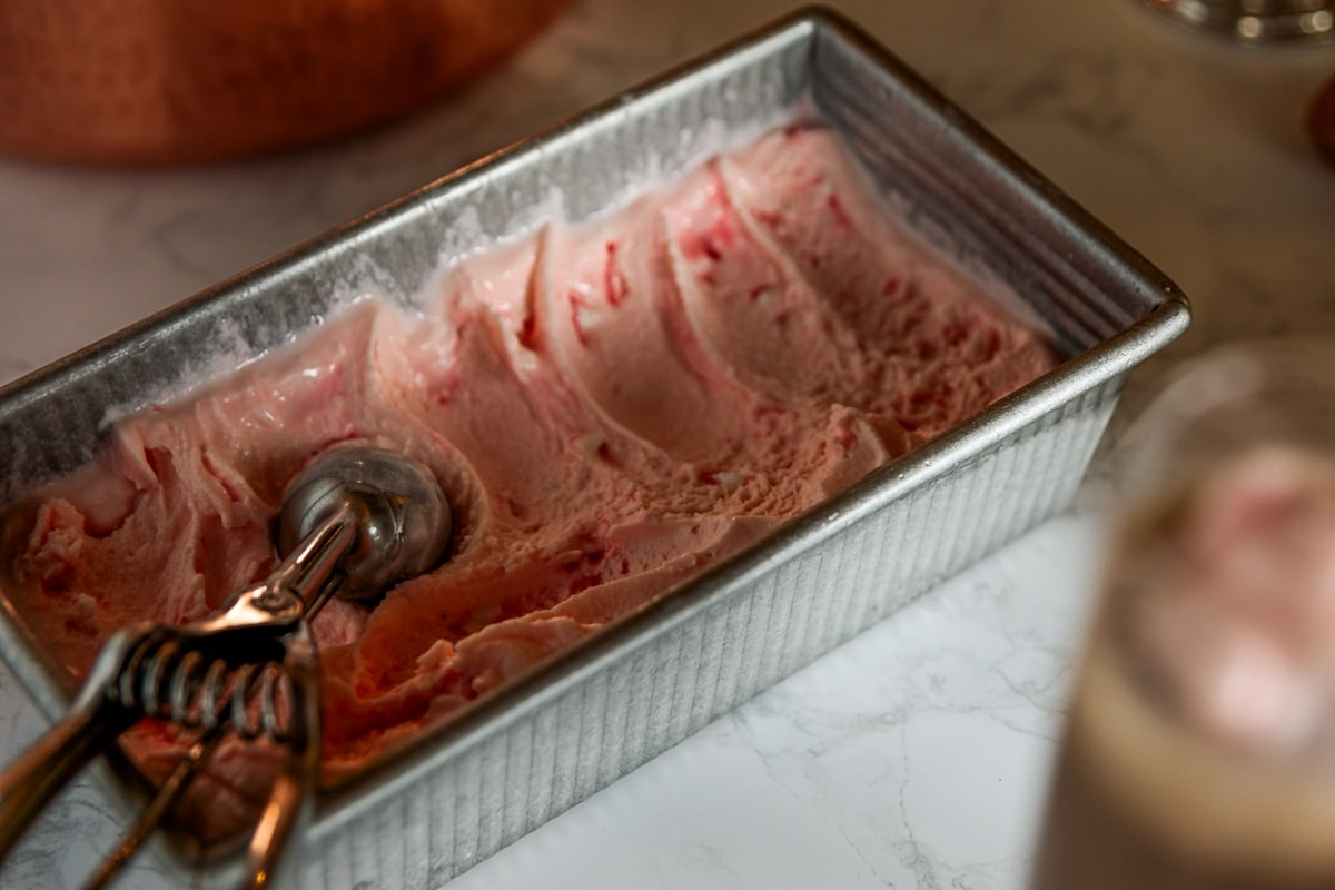 Rectangular metal container filled with pink peppermint ice cream with ice cream scoop resting on top all on marble surface