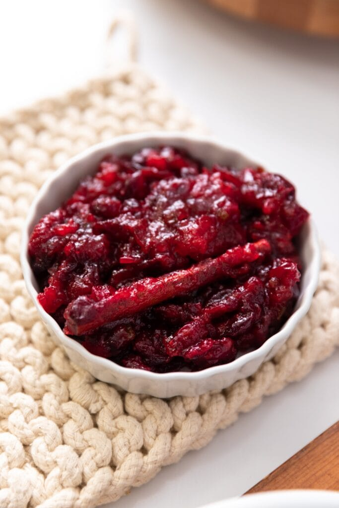 Close up view of red cranberry sauce with cinnamon stick all in white bowl sitting on off-white pot holder on white countertop