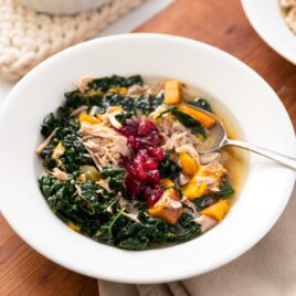 White bowl filled with turkey and kale soup with spoon sitting in broth all on wood surface with extra bowl of soup to the side