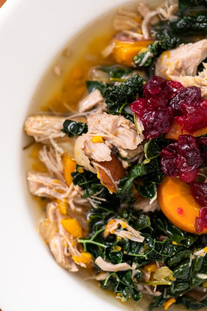 Close up top down view of turkey soup with kale and sweet potatoes and topped with a red cranberry sauce all in white bowl