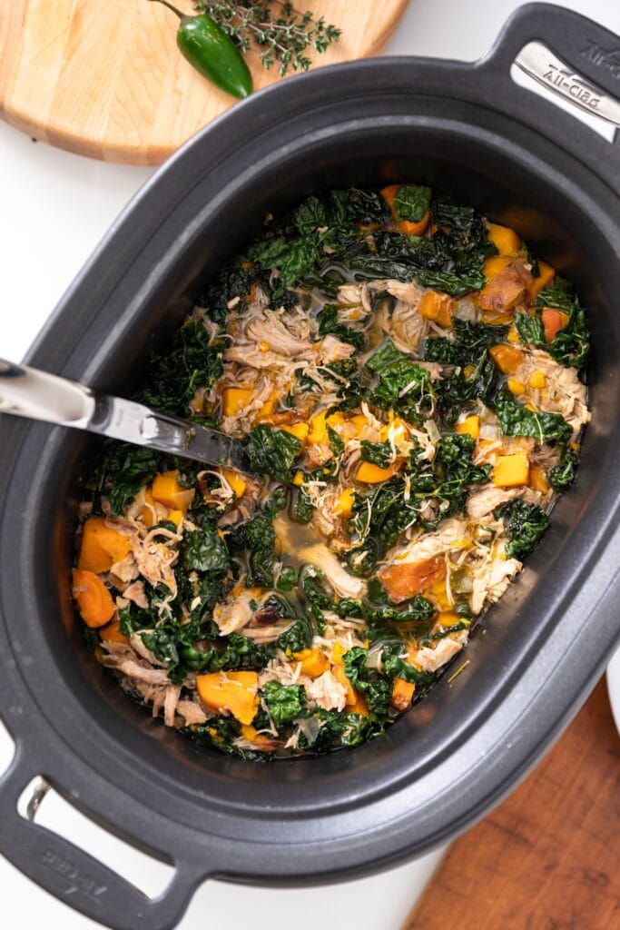 Top down view of turkey soup sitting in slow cooker with kale and sweet potatoes and ladle resting against side all on white countertop surface