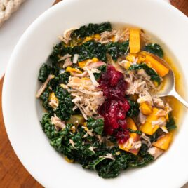 Top down view of slow cooker turkey soup served in a white bowl with soup spoon on the side amidst pieces of kale and sweet potato and topped with a cranberry sauce sitting on wood board with napkin underneath