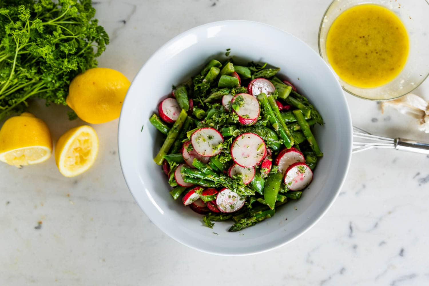 Top down view of asparagus salad with radish and sugar peas in a large white bowl with extra lemons, parsley, garlic and homemade vinaigrette on a marble surface