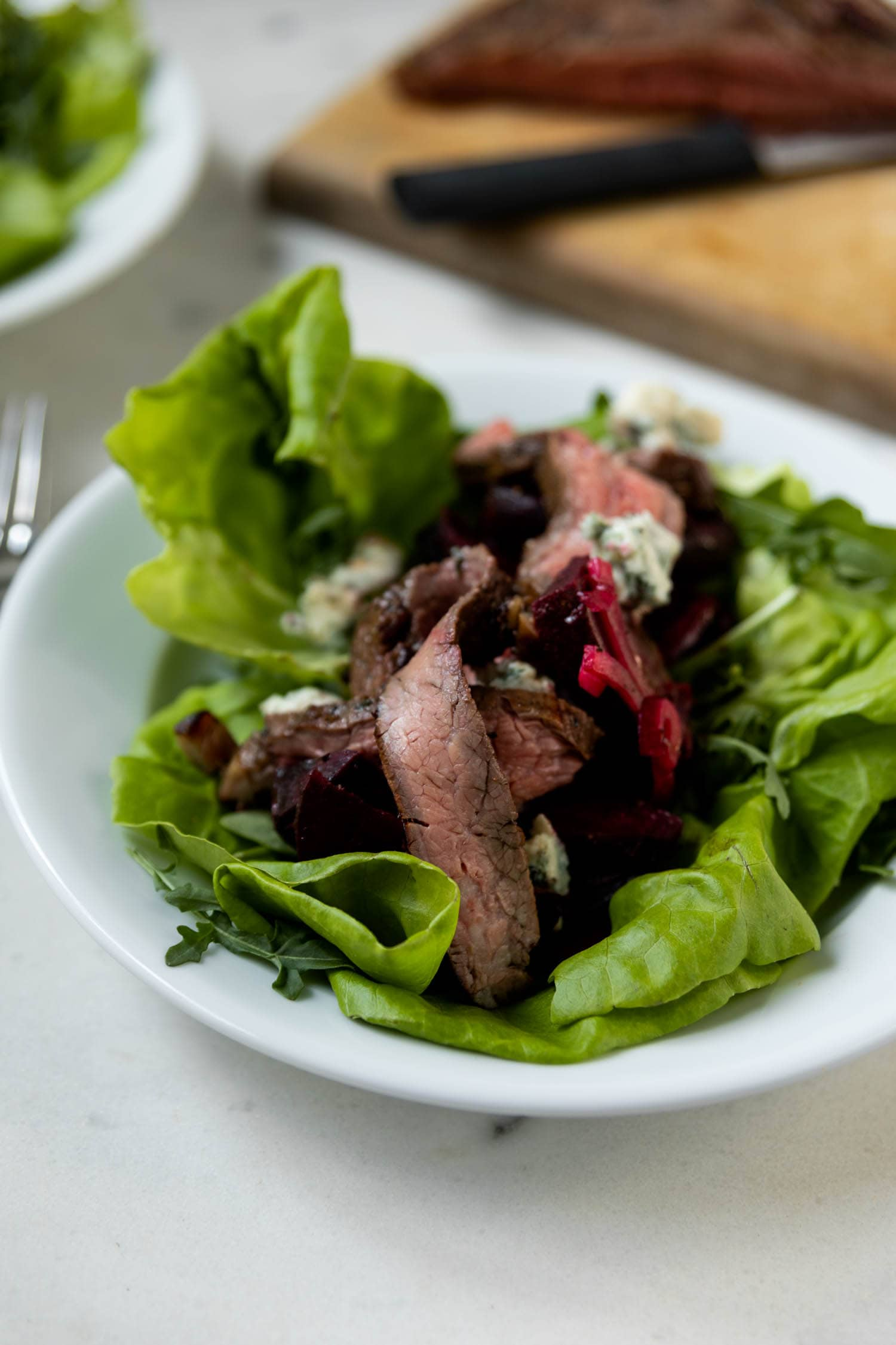 Butter lettuce and arugula topped with grilled flank steak, grilled beets and feta on a white plate with steak, cutting board and knife in background on a marble surface.