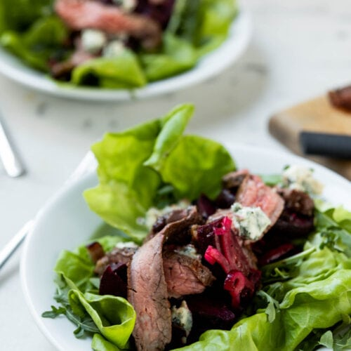 Butter lettuce and arugula topped with grilled flank steak, grilled beets and feta on a white plate with second plate filled with the same salad in background on a marble surface.