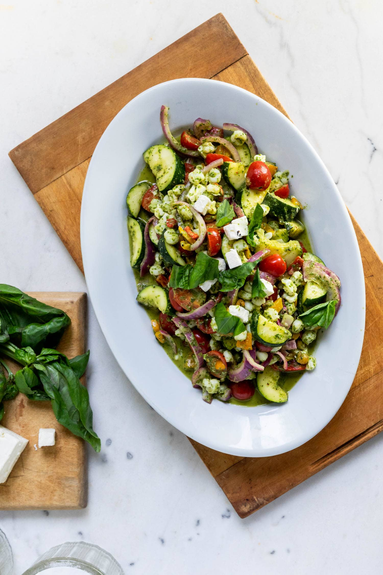 Top down view of grilled zucchini, onion and tomato salad topped with a basil dressing loaded in an Ironstone bowl with feta cheese and additional basil on a smaller cutting board all on a marble surface.