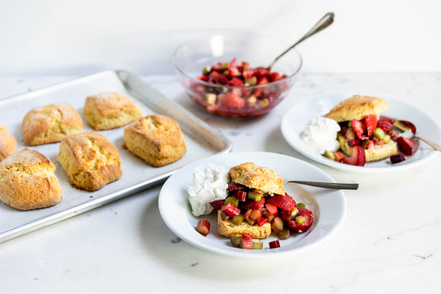 Strawberry and rhubarb shortcakes with whipped cream on two bowls with golden biscuits and macerated fruit in a bowl in the background on a marble surface