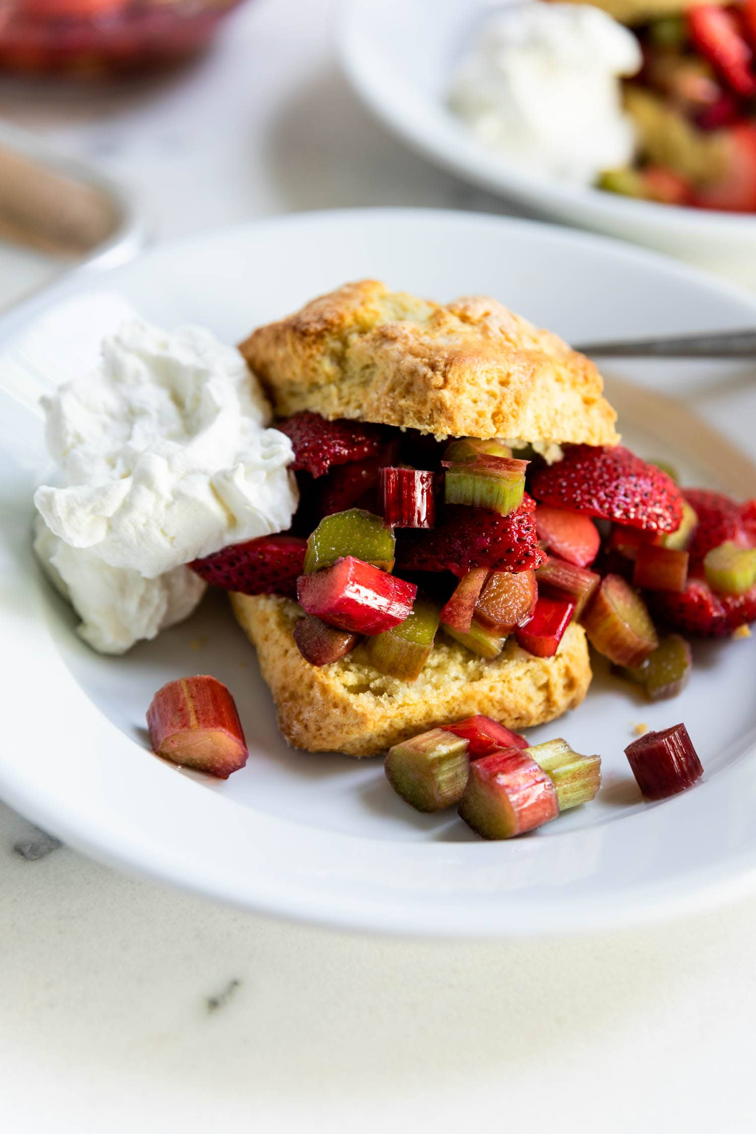 Strawberries, rhubarb and whipped cream on a bowl sandwiched between two golden biscuits on a marble surface