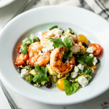Grilled tequila lime shrimp on a bed of cherry tomatoes, corn and cilantro and sprinkled with feta cheese with second plate, fork and linen towel in background on a marble surface