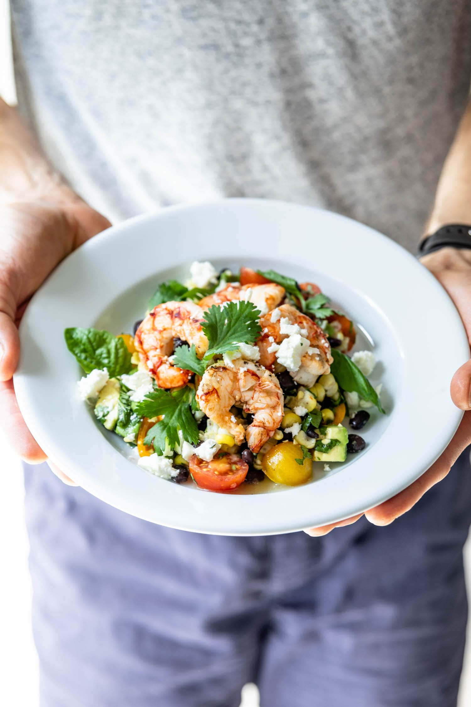 Two hands holding a plate of grilled tequila lime shrimp on a bed of cherry tomatoes, corn and cilantro and sprinkled with feta cheese