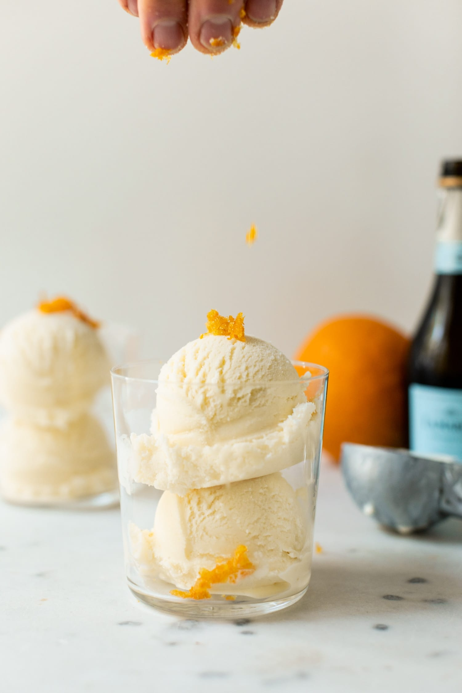 Mimosa ice cream being speckled with orange zest pieces from the top of the picture in a clear glass with second ice cream cup, orange, ice cream scoop and champagne bottle in background on a white marble surface