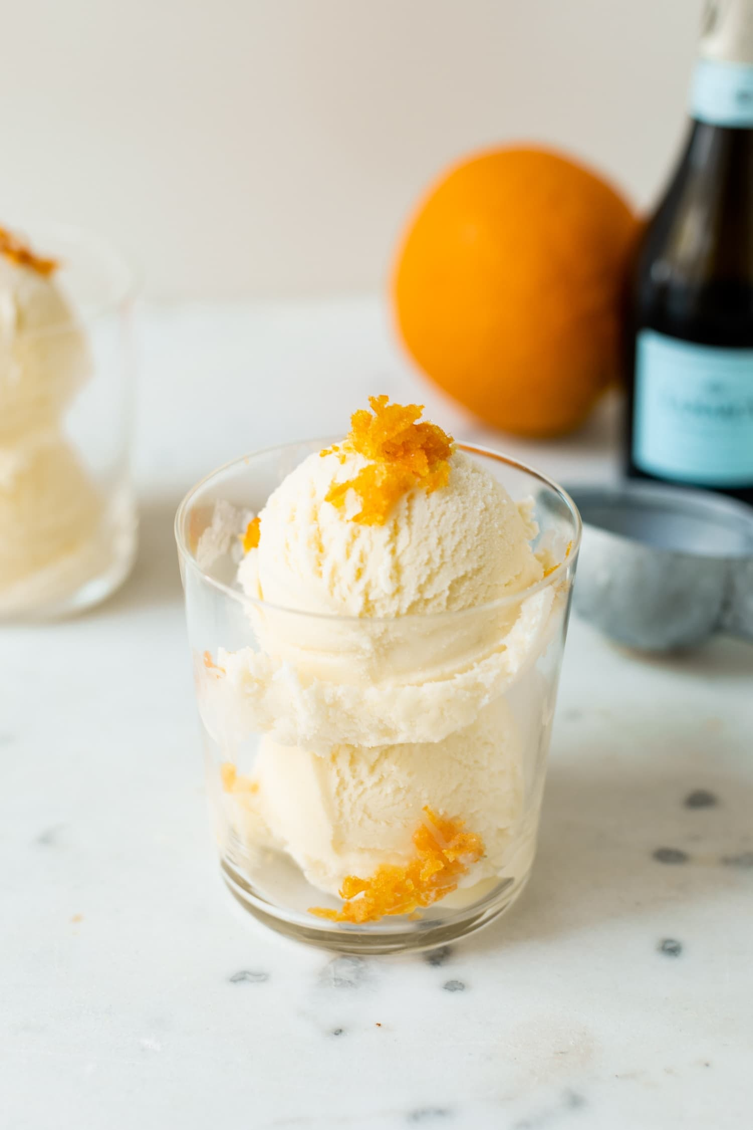 Mimosa ice cream speckled with orange zest pieces in a clear glass with second ice cream cup, orange, ice cream scoop and champagne bottle in background on a white marble surface