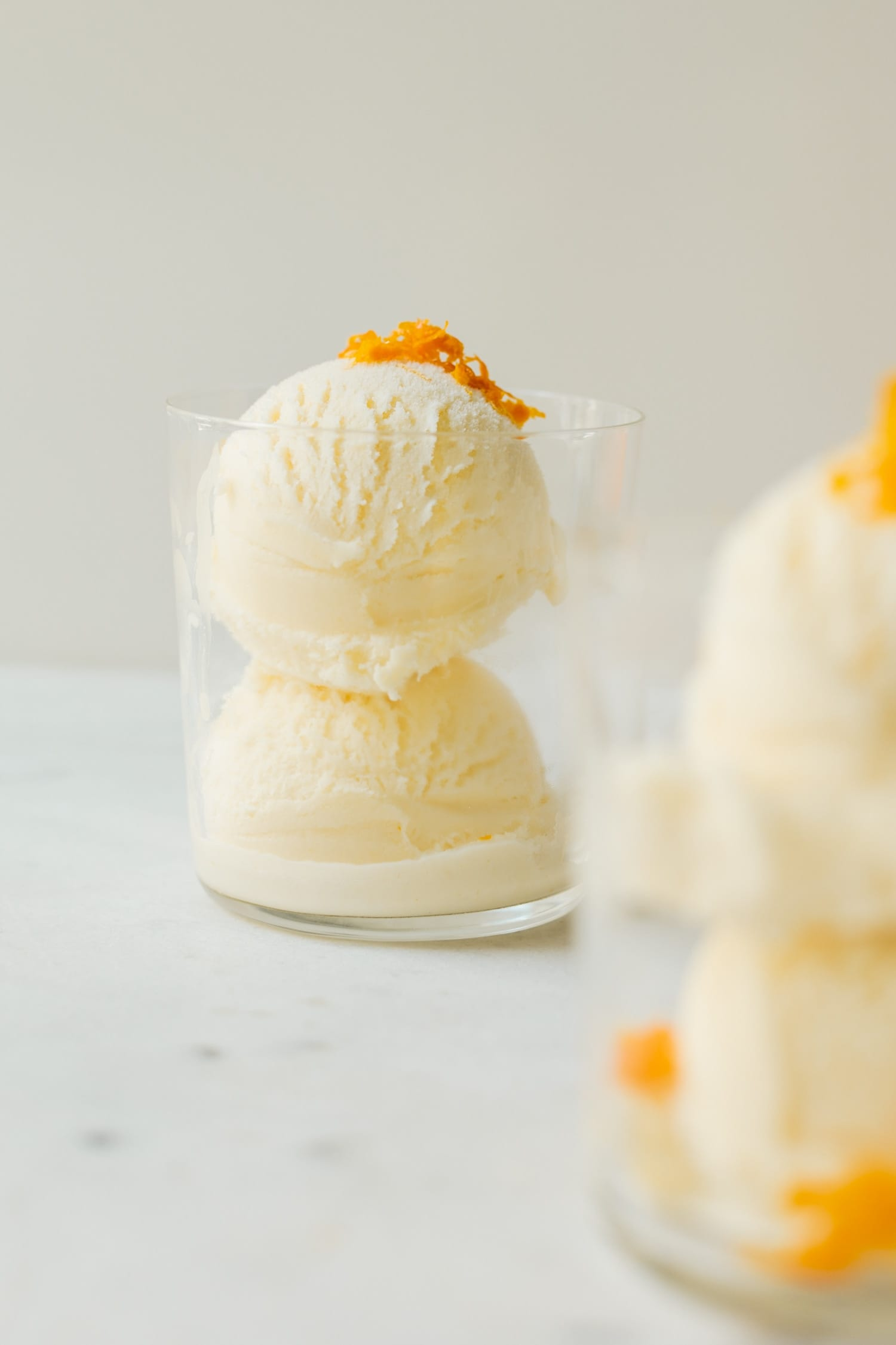 Mimosa ice cream speckled with orange zest pieces in a clear glass on marble surface with second ice cream glass in foreground