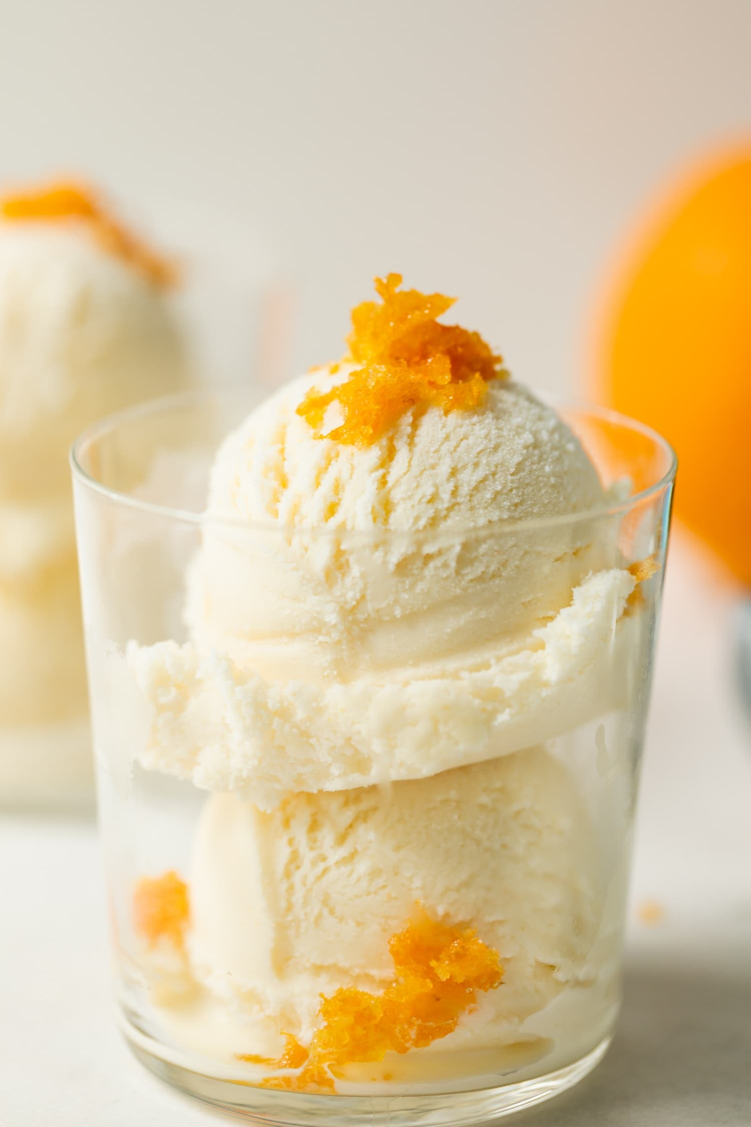 Mimosa ice cream speckled with orange zest pieces in a clear glass on marble surface with second ice cream glass and orange in background