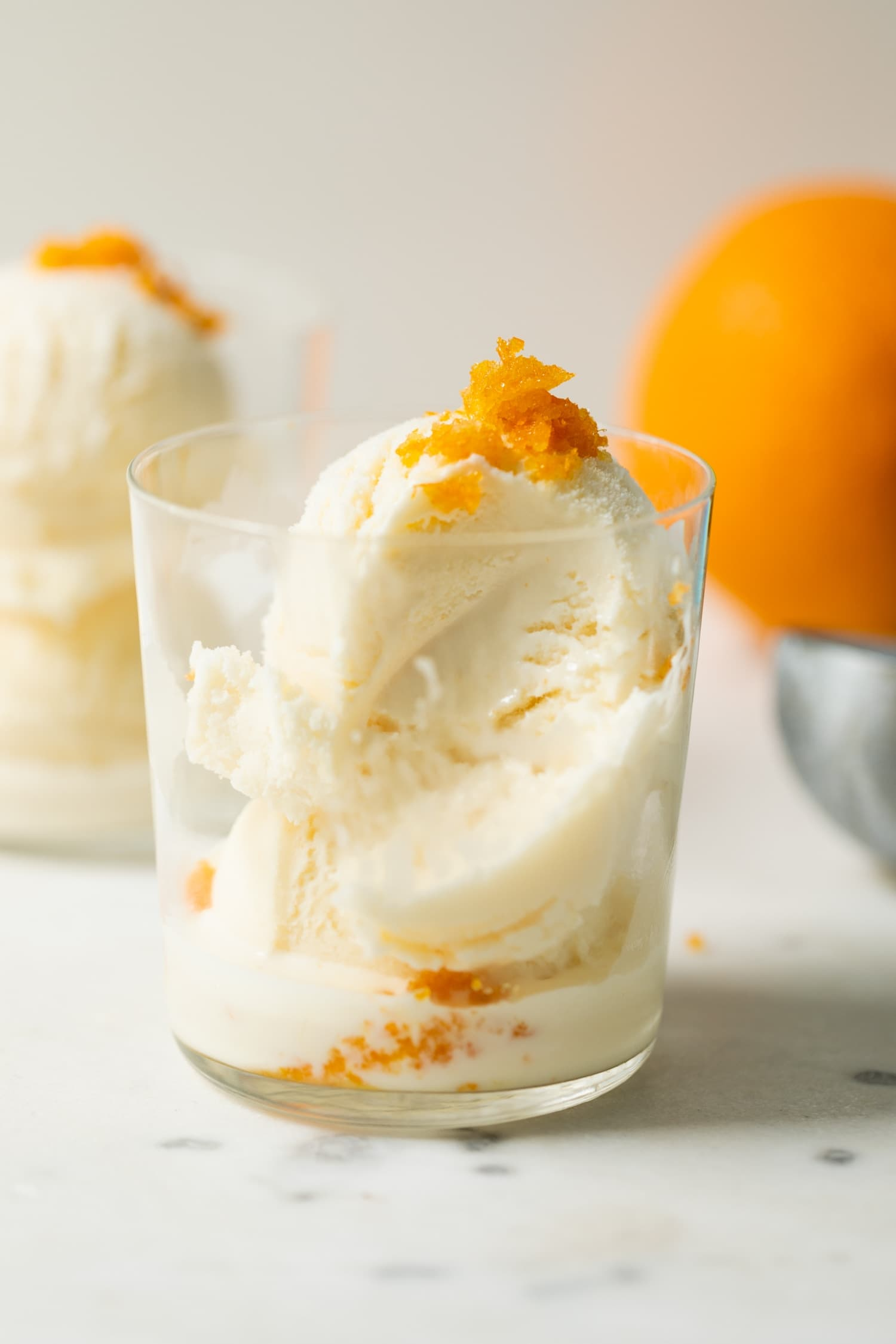 Mimosa ice cream speckled with orange zest pieces with a bite missing in a clear glass on marble surface with second ice cream glass and orange in background