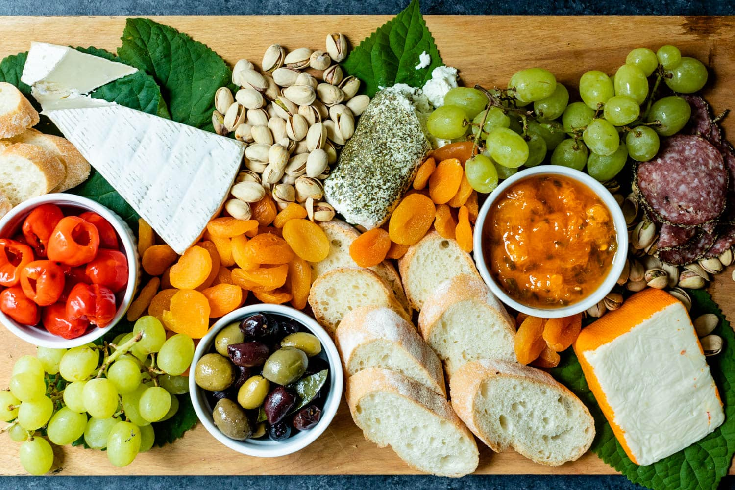 Top down view of peach jalapeno jam in a white bowl with a spoon surrounded by tomatoes, grapes, goat cheese, pistachios, olives, bread, dried apricots and meat all on a brown serving board with green leaves in the background