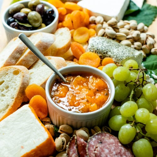 Peach jalapeño jam with a spoon in a white bowl surrounded by grapes, bread, dried apricots, cheese, olives, tomatoes and goat cheese on a brown serving board