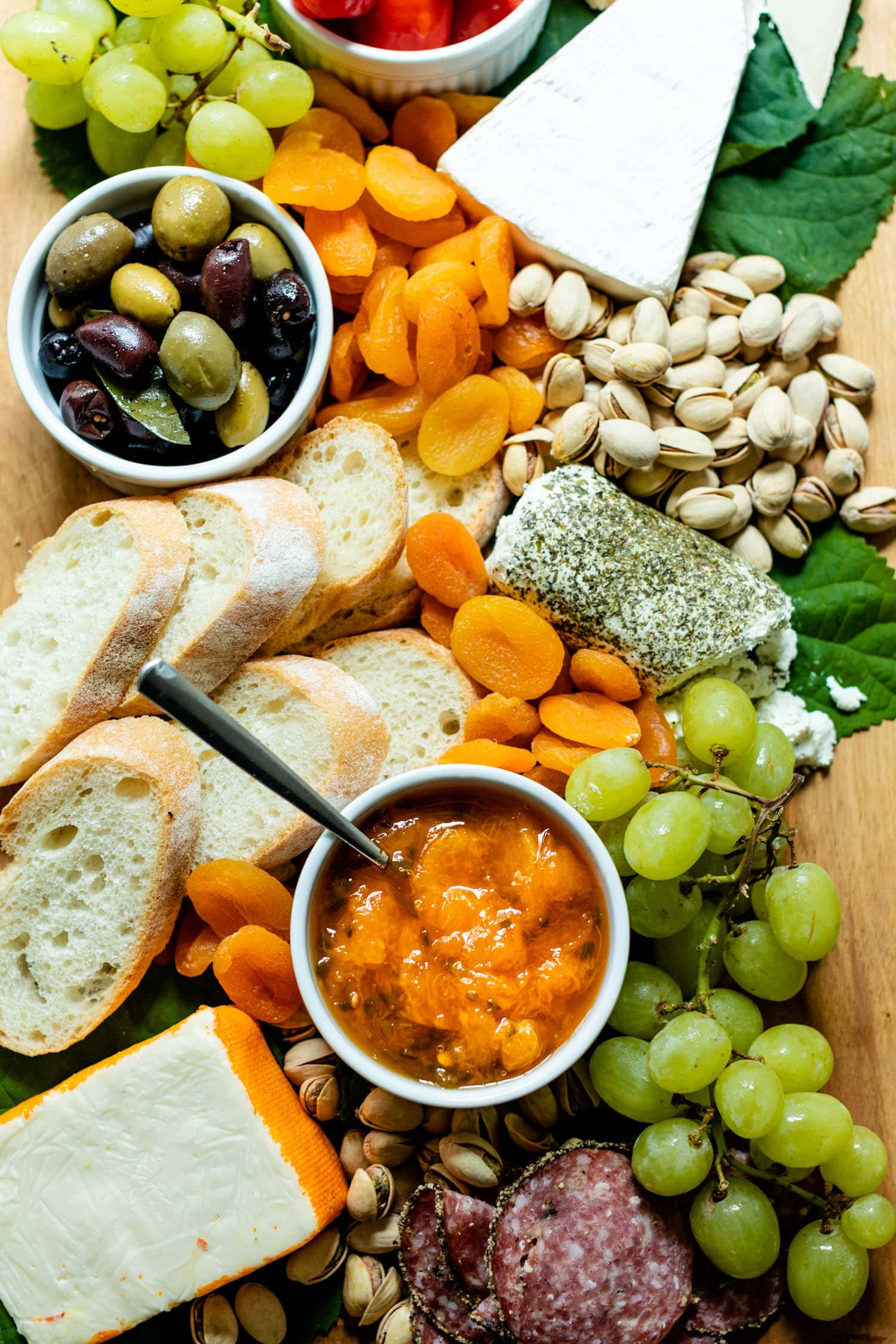Top down view of peach jalapeño jam with a spoon in a white bowl surrounded by grapes, olives, pistachios, bread, dried apricots, cheese and goat cheese on a brown serving board