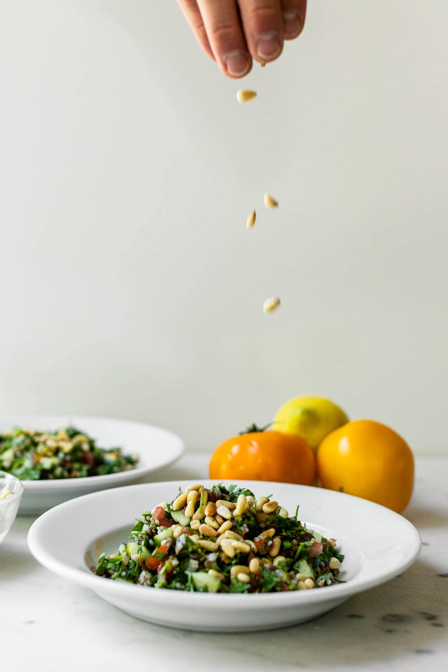 Bowl full of tabbouleh topped with pine nuts with hand at top of picture sprinkling more pine nuts on top with tomatoes and second bowl in background on marble surface