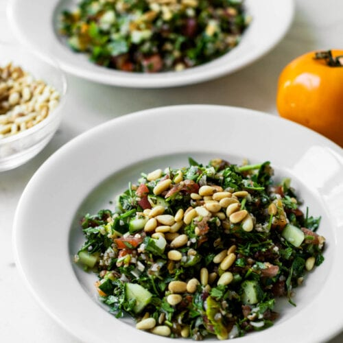 Two white bowls filled with tabbouleh topped with pine nuts with glass bowl of extra pine nuts and tomatoes to the side on a marble surface