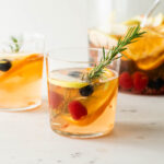 White sangria with a sprig of rosemary with blueberries, raspberries, mandarin orange pieces and apple splices with pitcher full of sangria in background on a marble surface