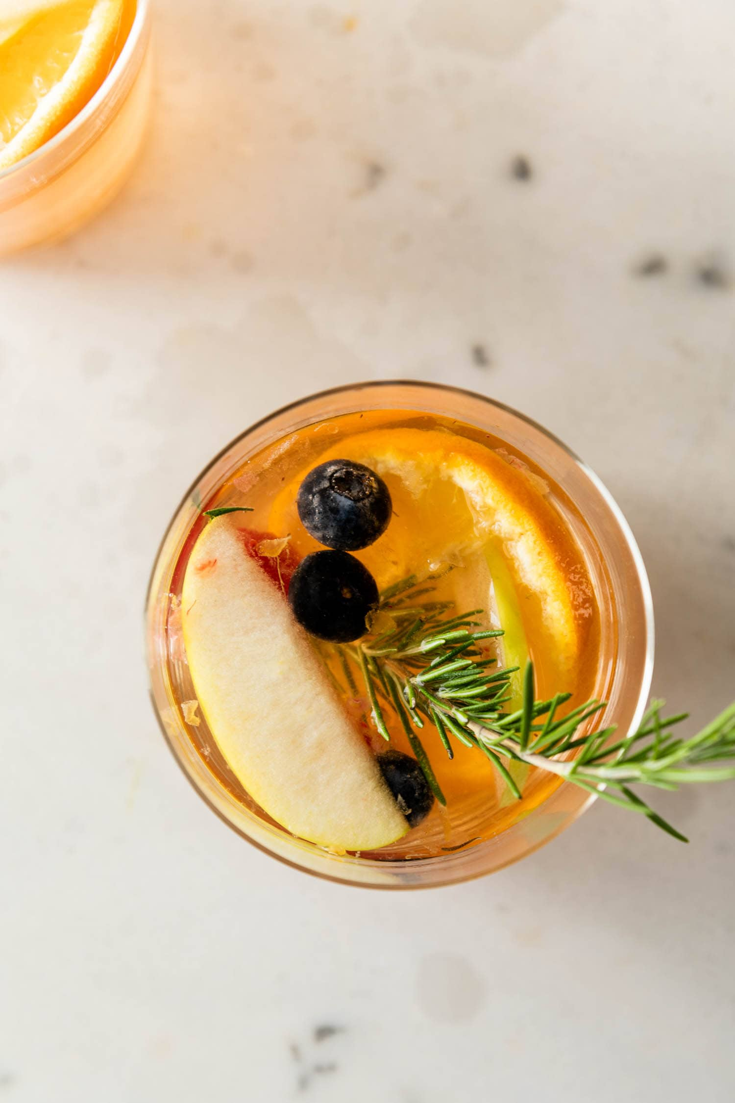 Top down shot of white sangria with a rosemary sprig and blueberries, mandarin orange and apple slice on a marble background