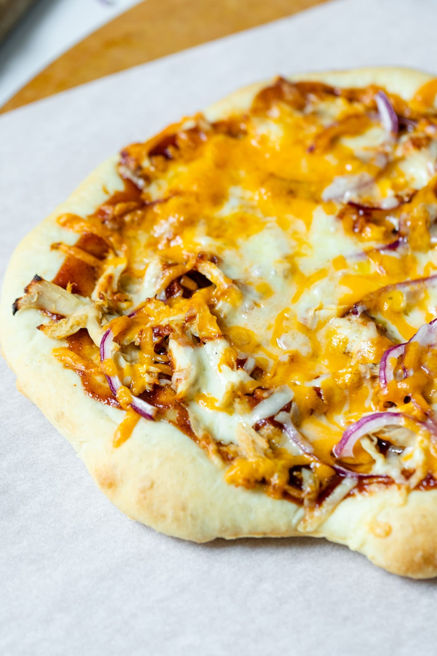 Homemade barbecue chicken pizza made of chicken, cheese, barbecue sauce and red onion on a homemade crust on a piece of white parchment and pizza board on a marble surface