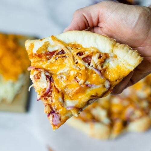 Slice of homemade barbecue chicken pizza with cheese, red onions, chicken, barbecue sauce and homemade crust being held with rest of pizza on a piece of parchment, pizza board, extra cheese on a cutting board and extra barbecue sauce in background on a marble surface
