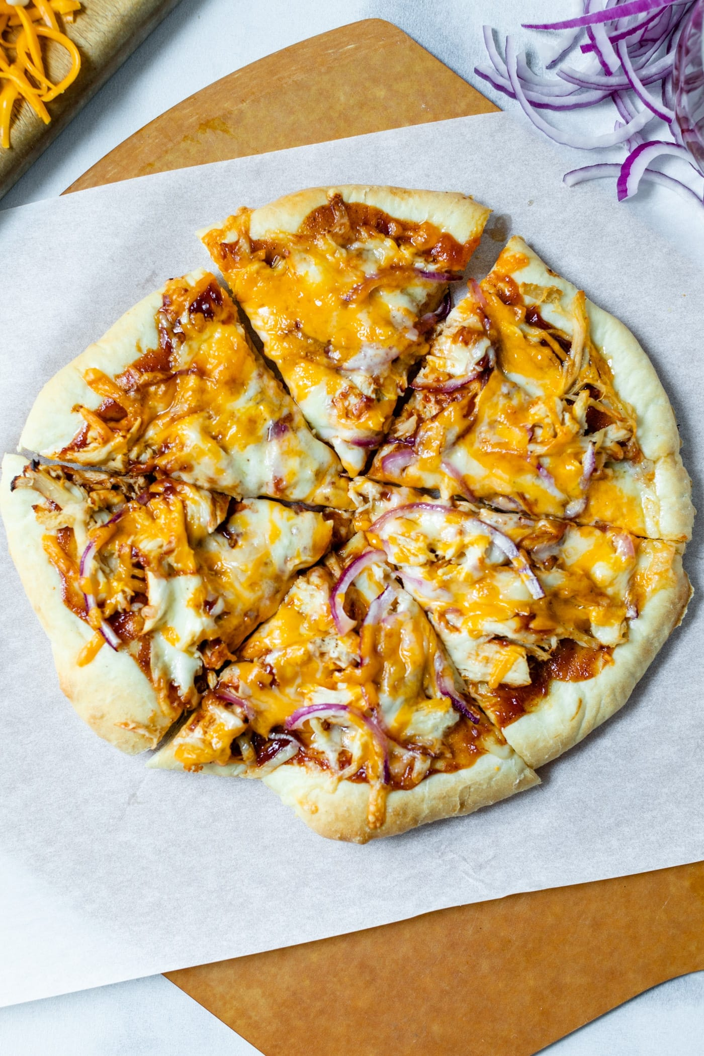 Top down view of sliced homemade barbecue chicken pizza made of chicken, cheese, barbecue sauce and red onion on a homemade crust on a piece of white parchment and pizza board with extra red onions and cheese on cutting board all on a marble surface