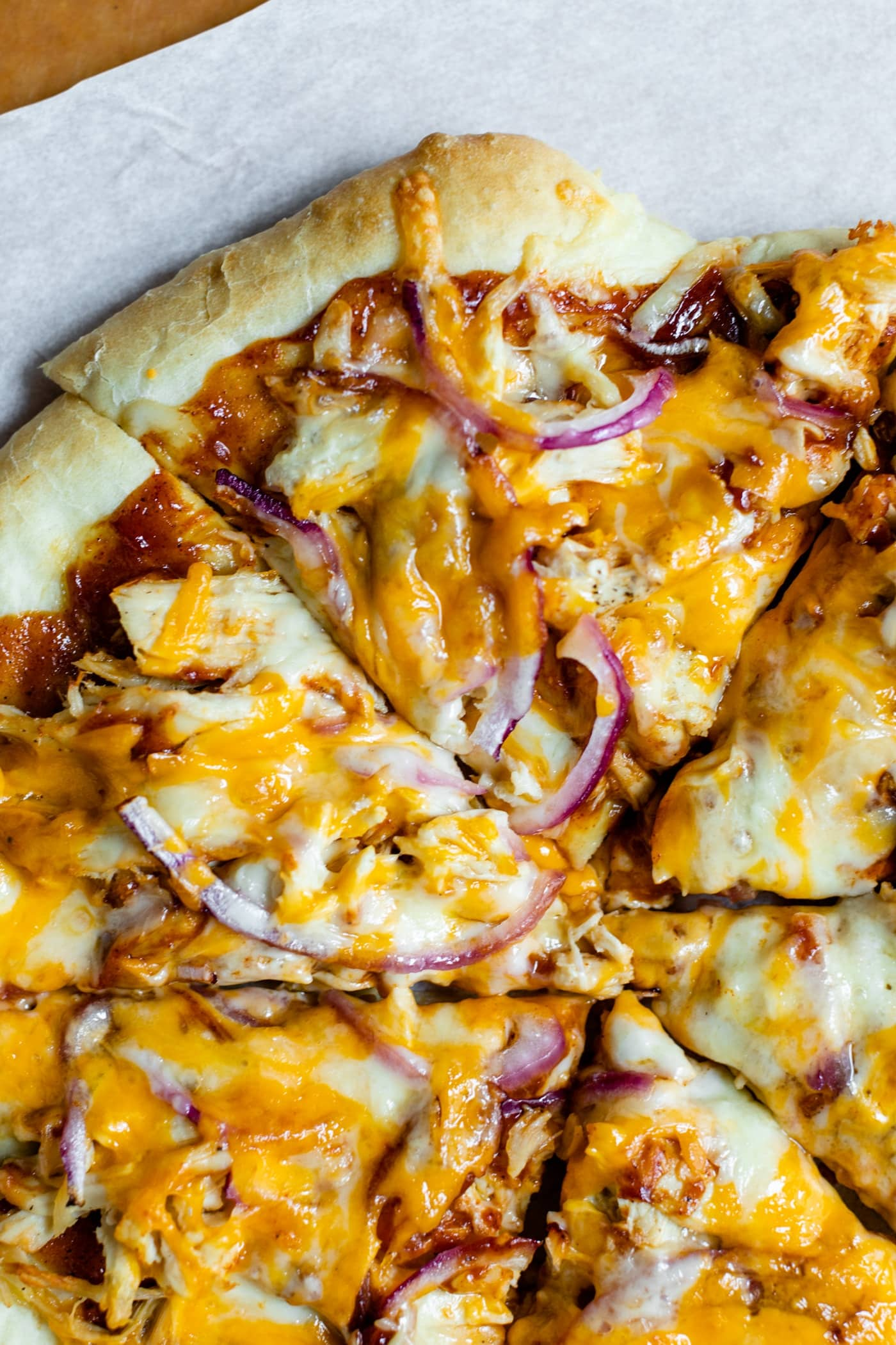 Top down view of sliced homemade barbecue chicken pizza made of chicken, cheese, barbecue sauce and red onion on a homemade crust on a piece of white parchment and pizza board